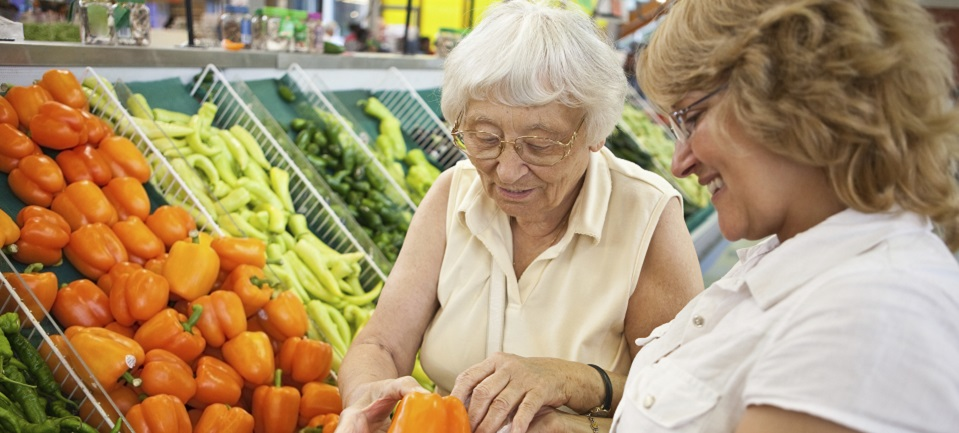 Direct car worker assists an older client with shopping in the supermarket