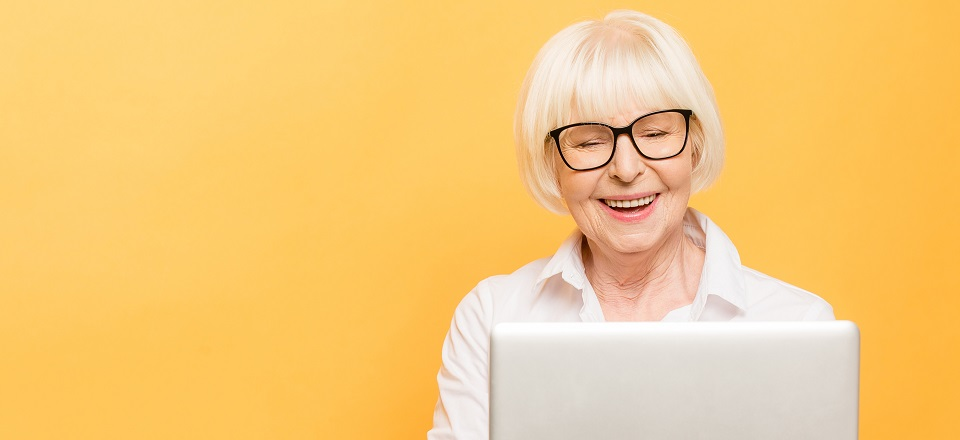Smiling woman holding a computer with yellow background.