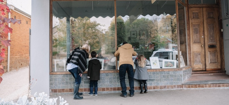 A family admiring a historical shop front