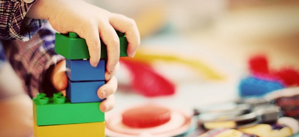 Image: Child plays with colourful Duplo blocks  Link to child page: Playgroups