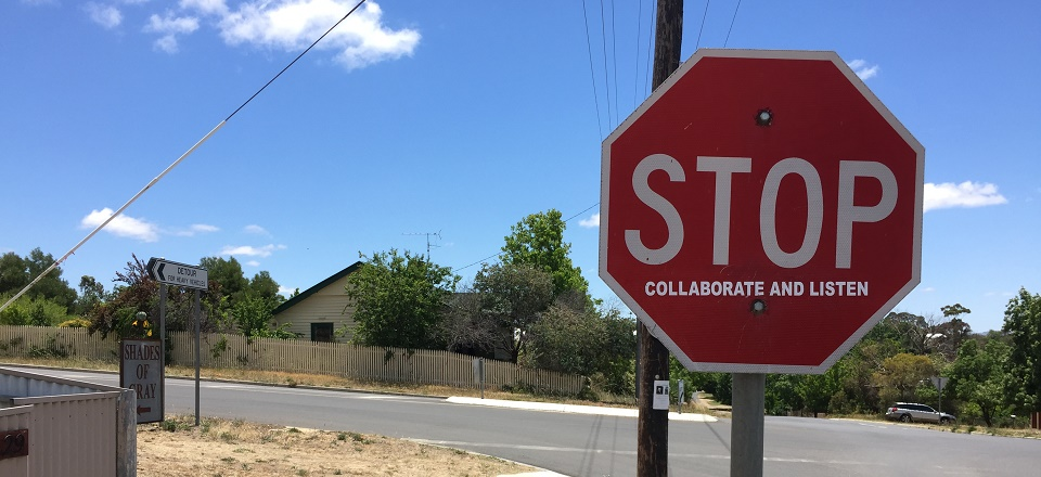 Stop sign - reads stop collaborate and listen.