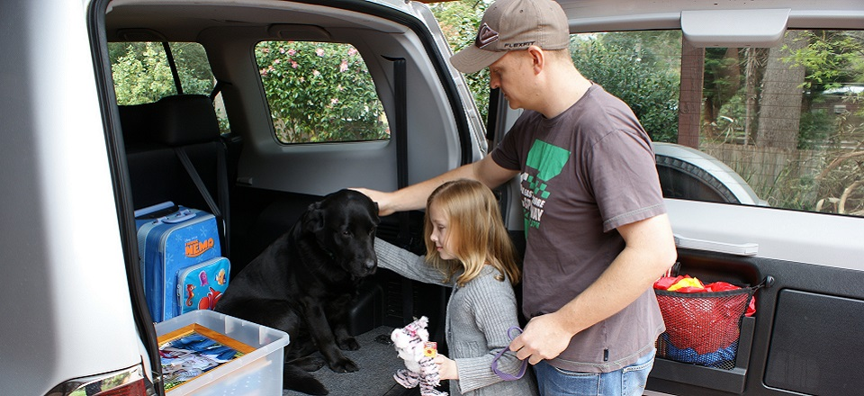 Image: A child and adult pack their car including their black Labrador dog.  Link to child page: Emergency Management