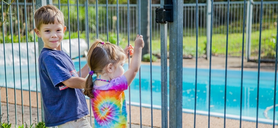 Kids standing at pool fence.