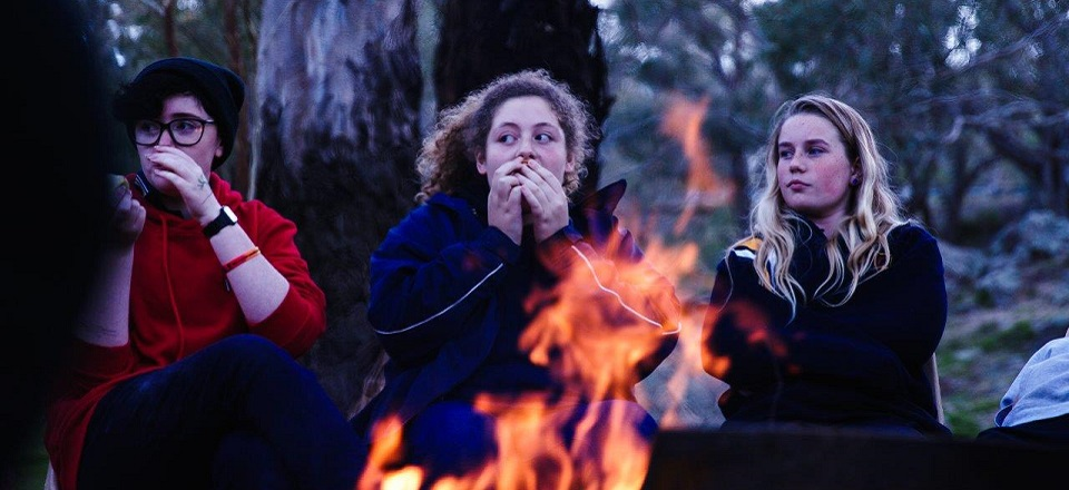 Image: Young people outdoors around a fire.  Link to child page: Young people