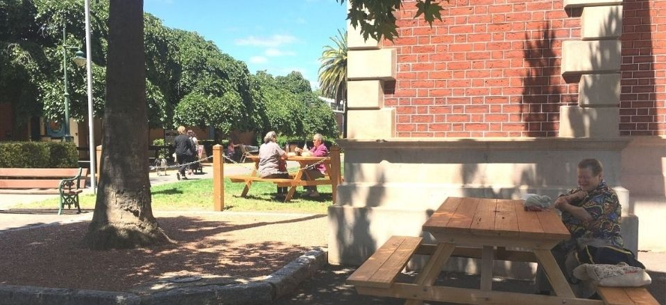 People enjoying the hand-made picnic tables, located next to the Castlemaine Visitor Information Centre.