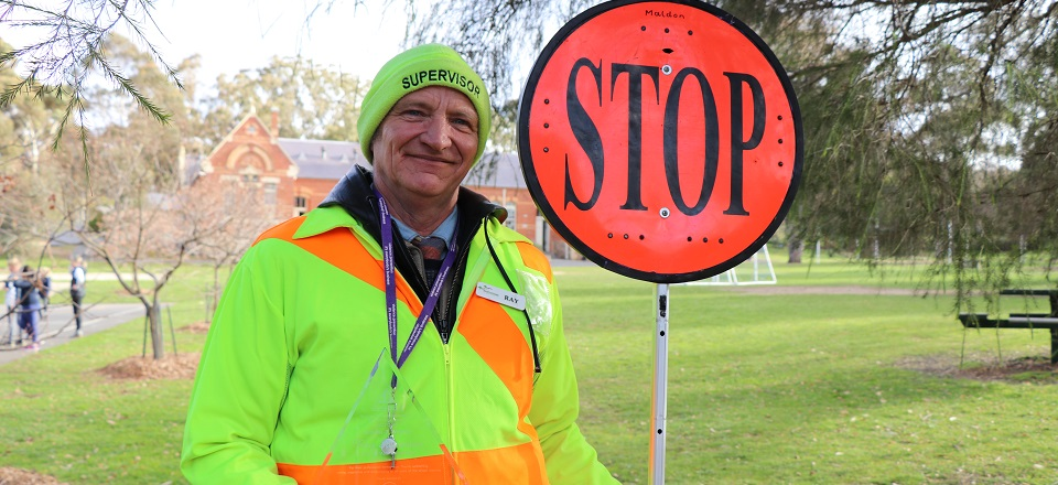 Image: Crossing supervisor Ray with stop sign and award.  Link to child page: School crossing safety