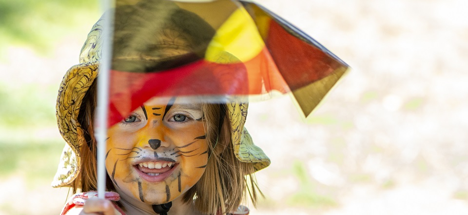 Smiling girl with tiger facepaint and Aboriginal flag